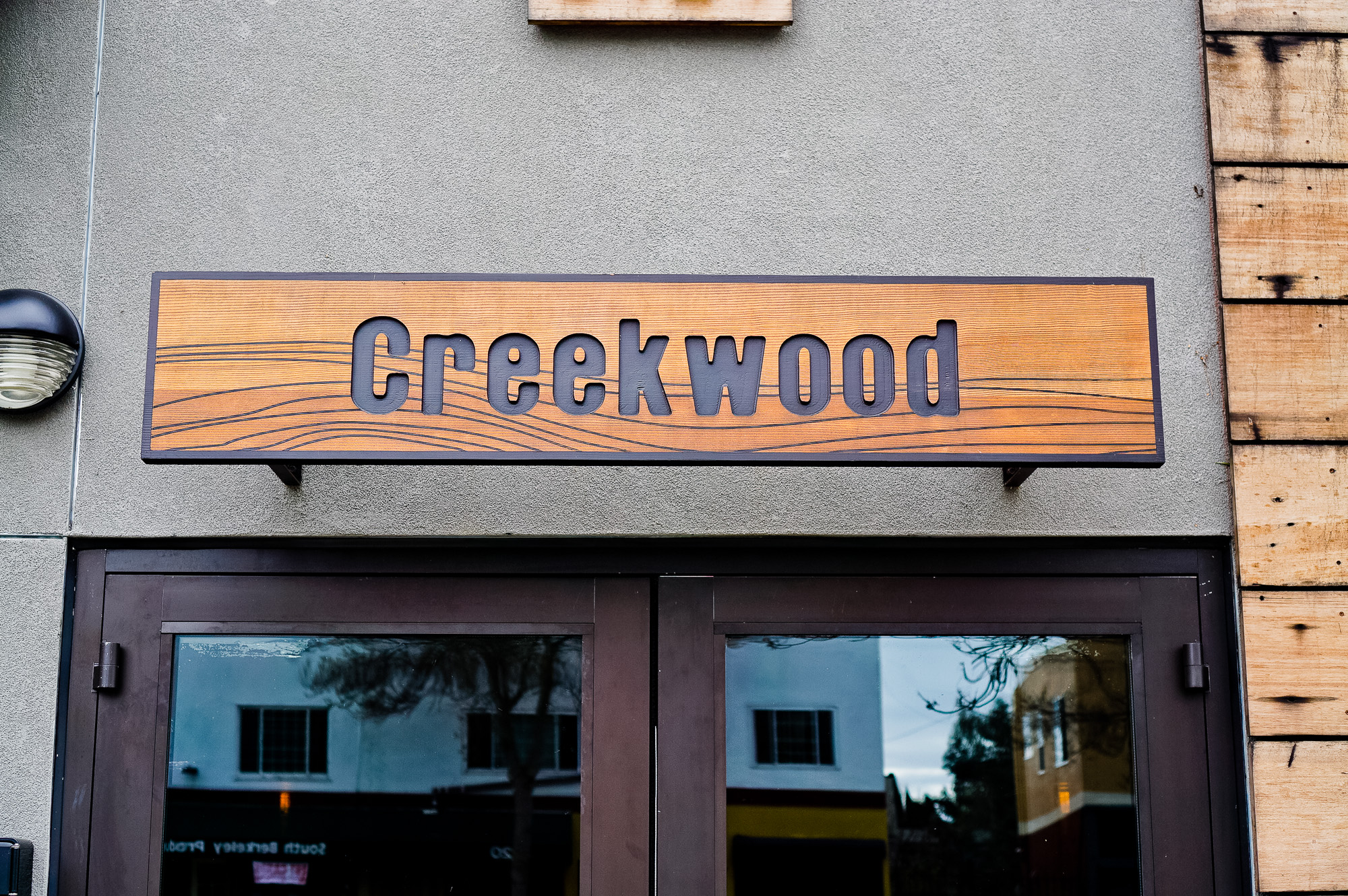 Engraved cedar wood sign on concrete walkl for Creekwood, a Californian-Italian restaurant in Berkeley, CA