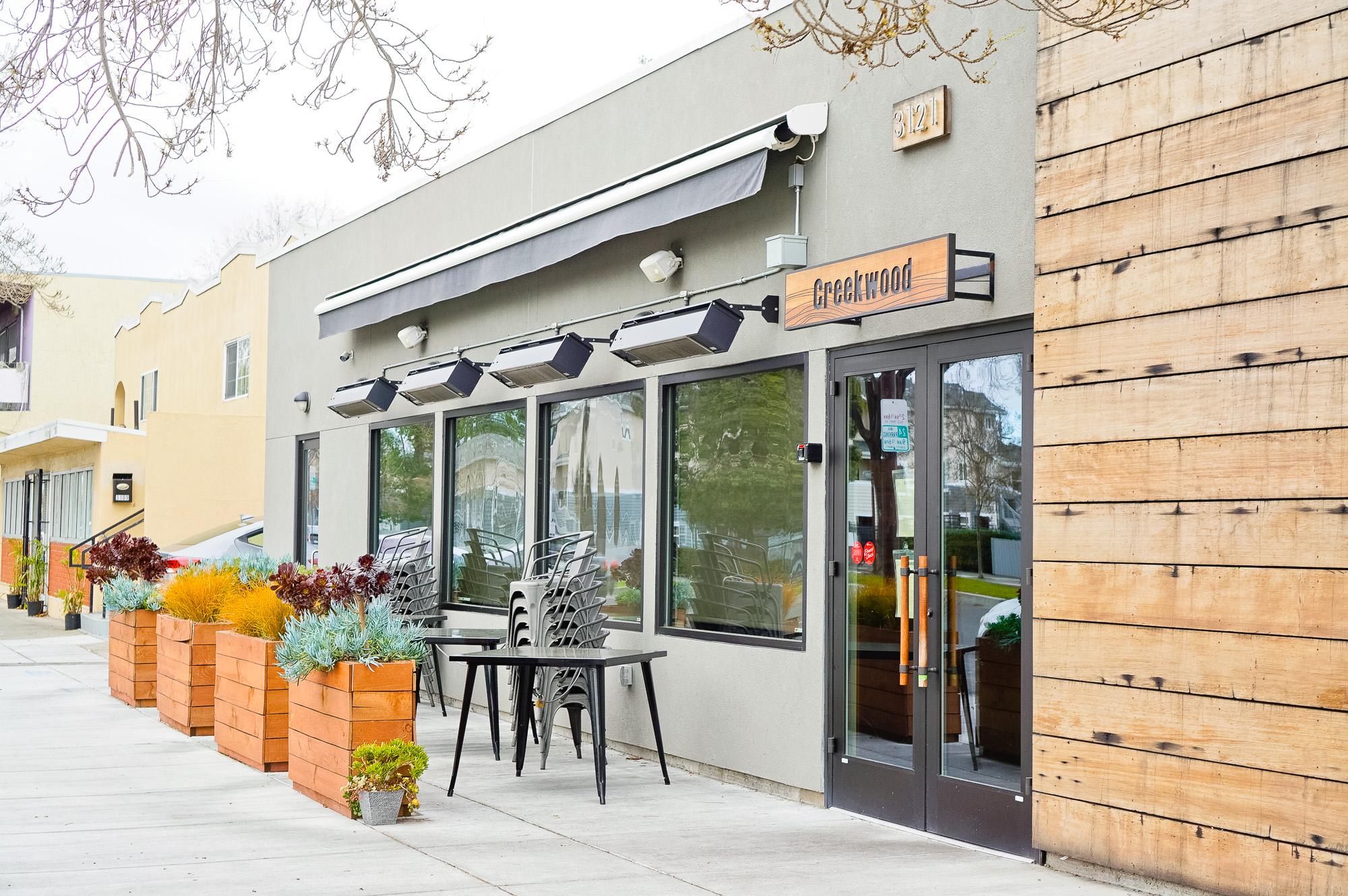 Engraved cedar wood sign on concrete walkl for Creekwood, a Californian-Italian restaurant in Berkeley, CA
