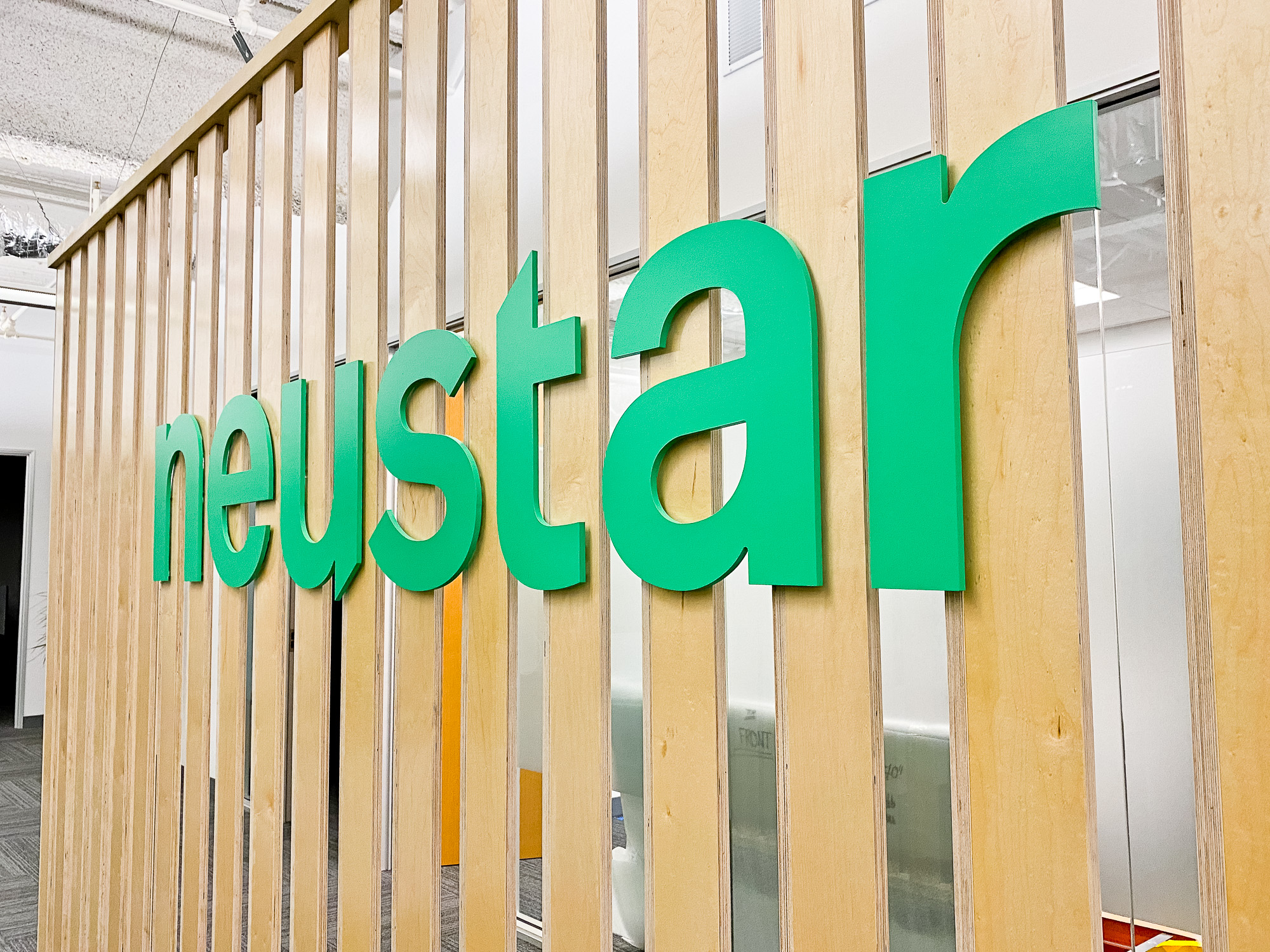 Wood slat dividing wall wiht green logo for lobby/reception desk area at the San Francisco office of Neustar, an American technology company that provides real-time information and analytics.