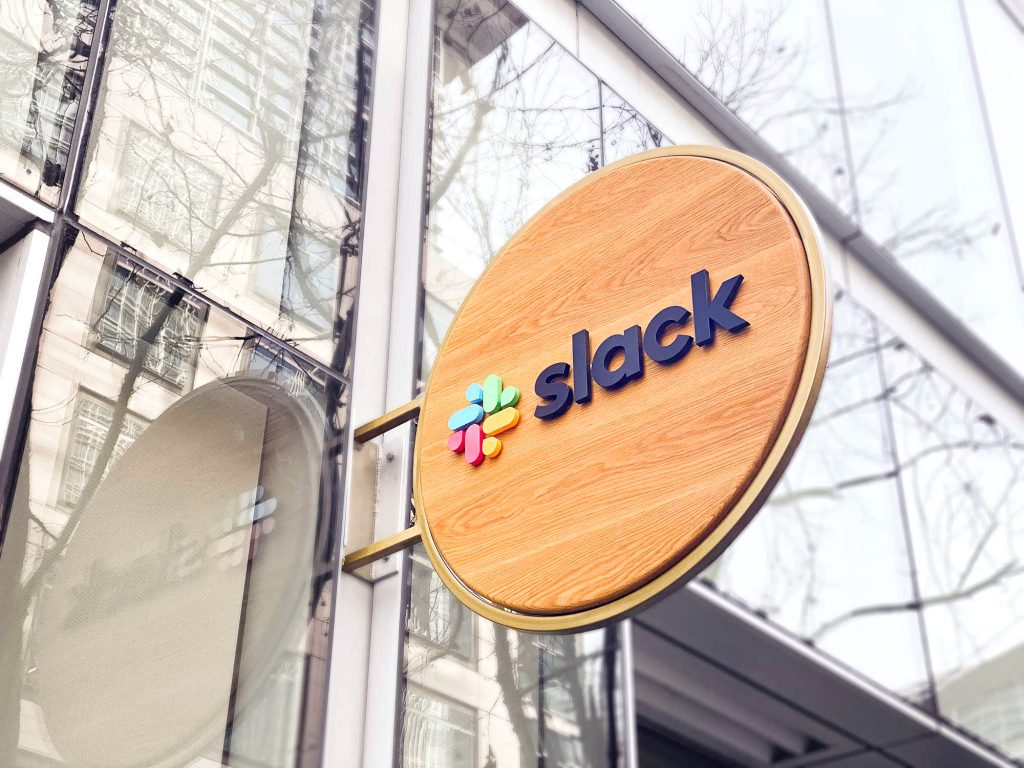 Wood blade sign with dimensional color logo and brass hardware for the San Francisco brand space at Slack, an American cloud-based set of team collaboration tools and services.