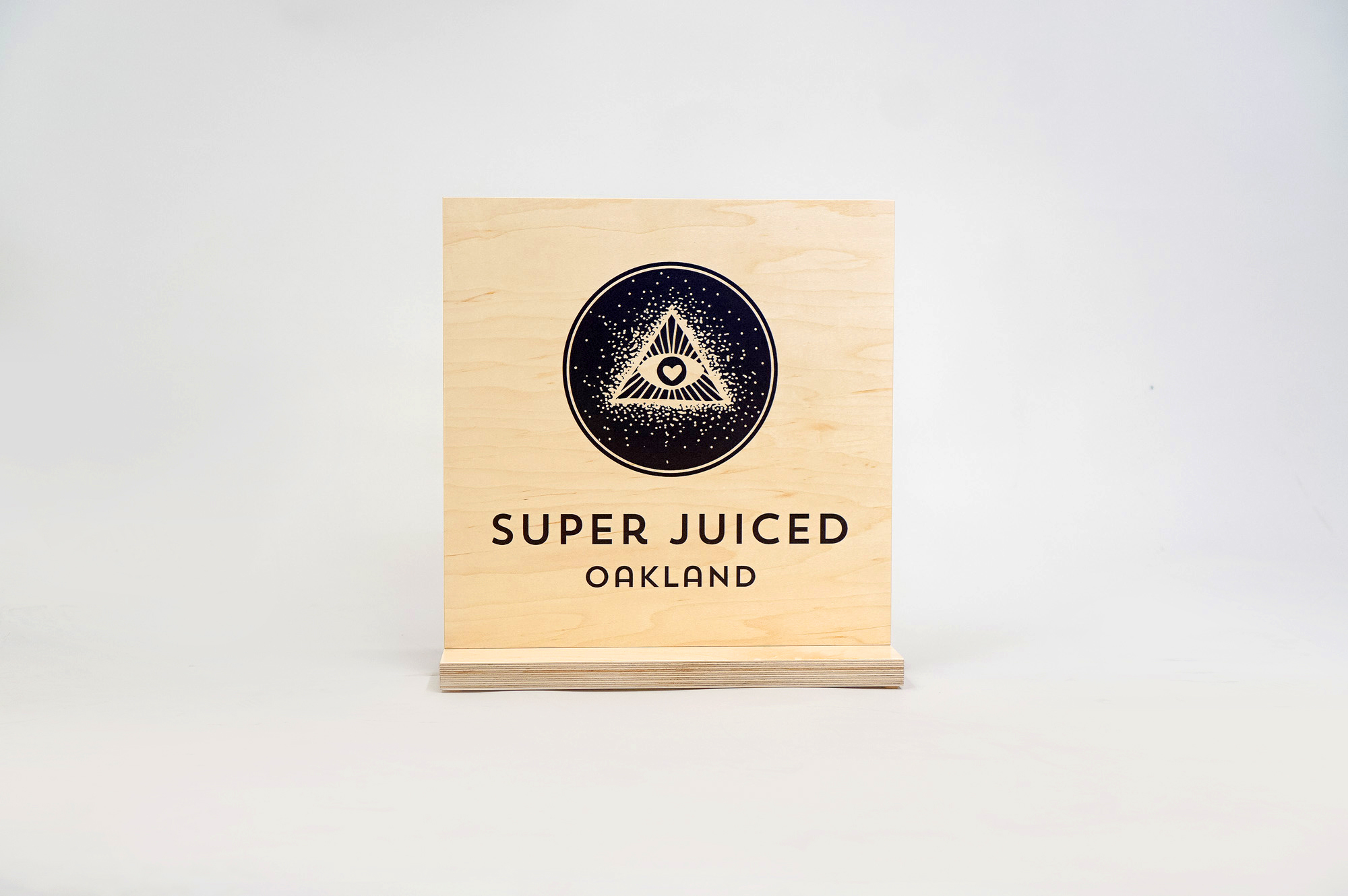 Light wood tabletop sign with black print for the retail location of Super Juiced, an organic juice and smoothie bar in Old Oakland.
