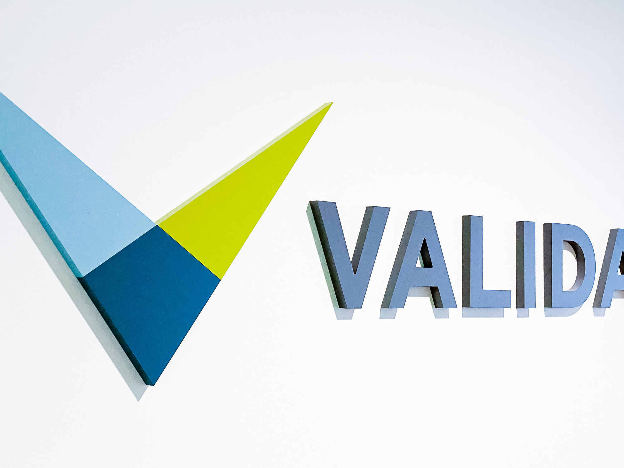 Full color dimensional logo on white wall for the lobby of Validant, a San Francisco based company that delivers end-to-end quality, compliance, and regulatory consulting service for healthcare companies around the world.