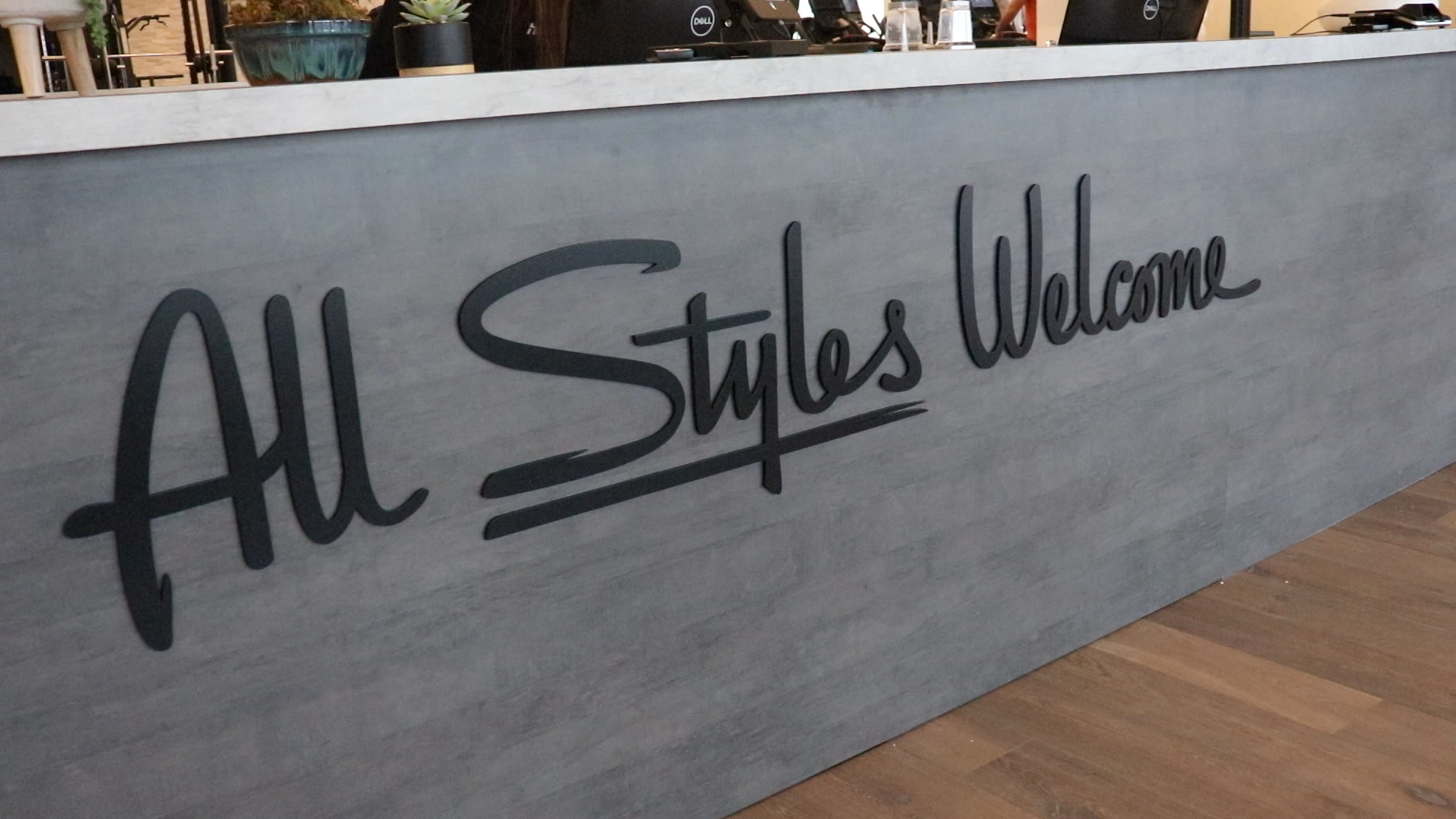 Black script front desk sign for the lobby at Styles Studios, a fitness club in Peoria, IL.
