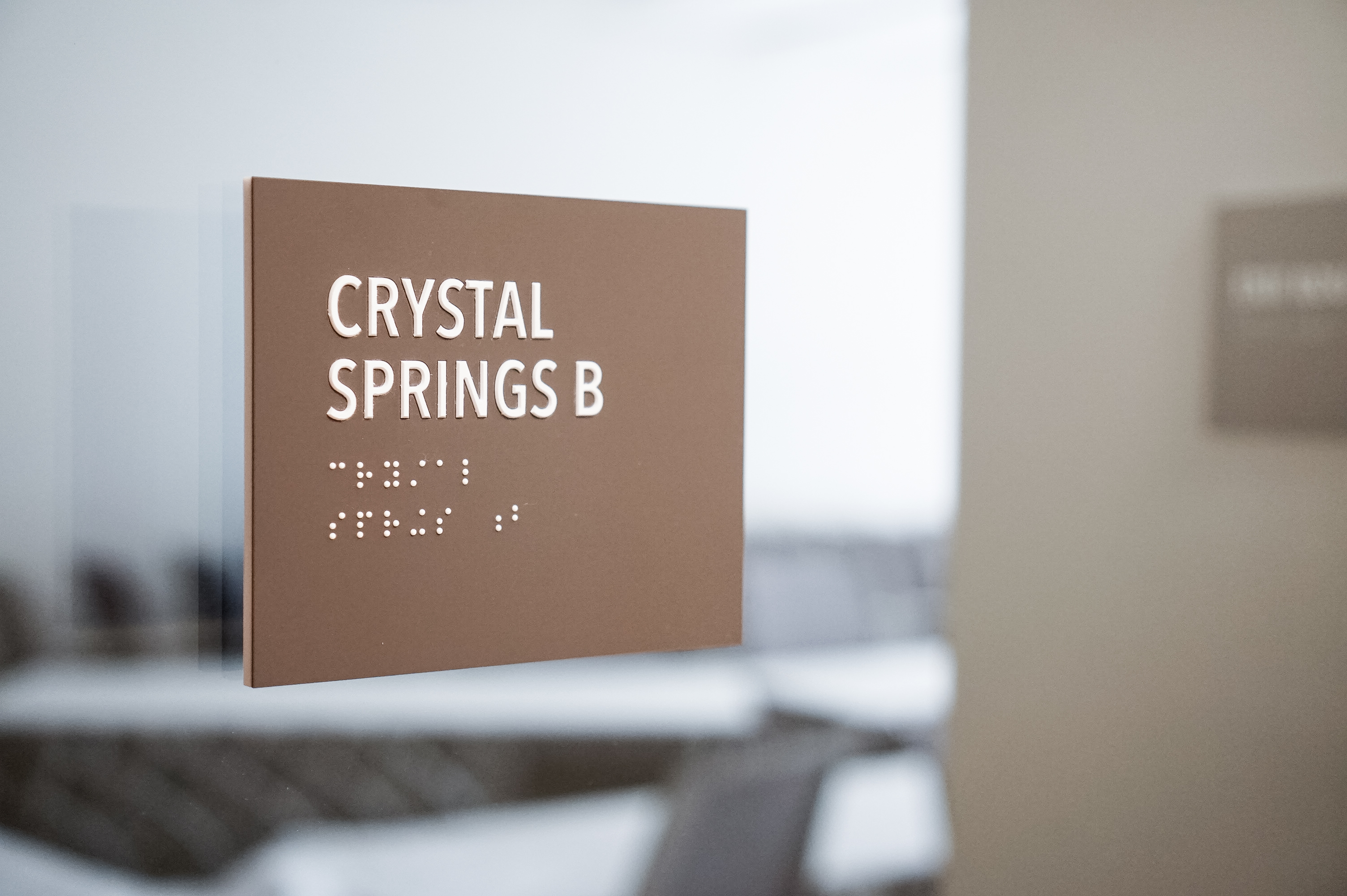 Minimal grey office ADA room signs for Baker McKenzie, a multinational law firm.