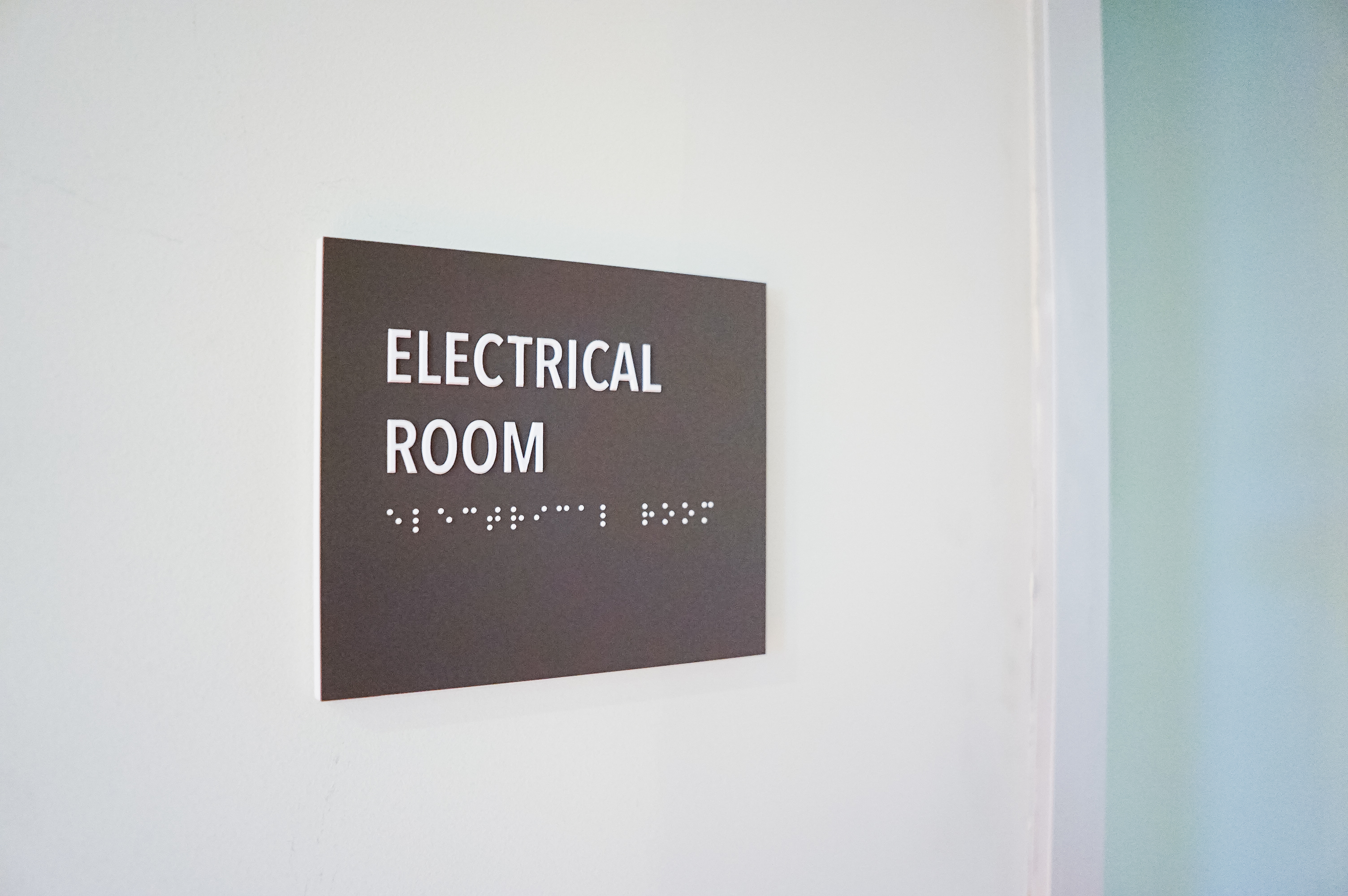 Minimal grey office ADA electrical room sign for Baker McKenzie, a multinational law firm.