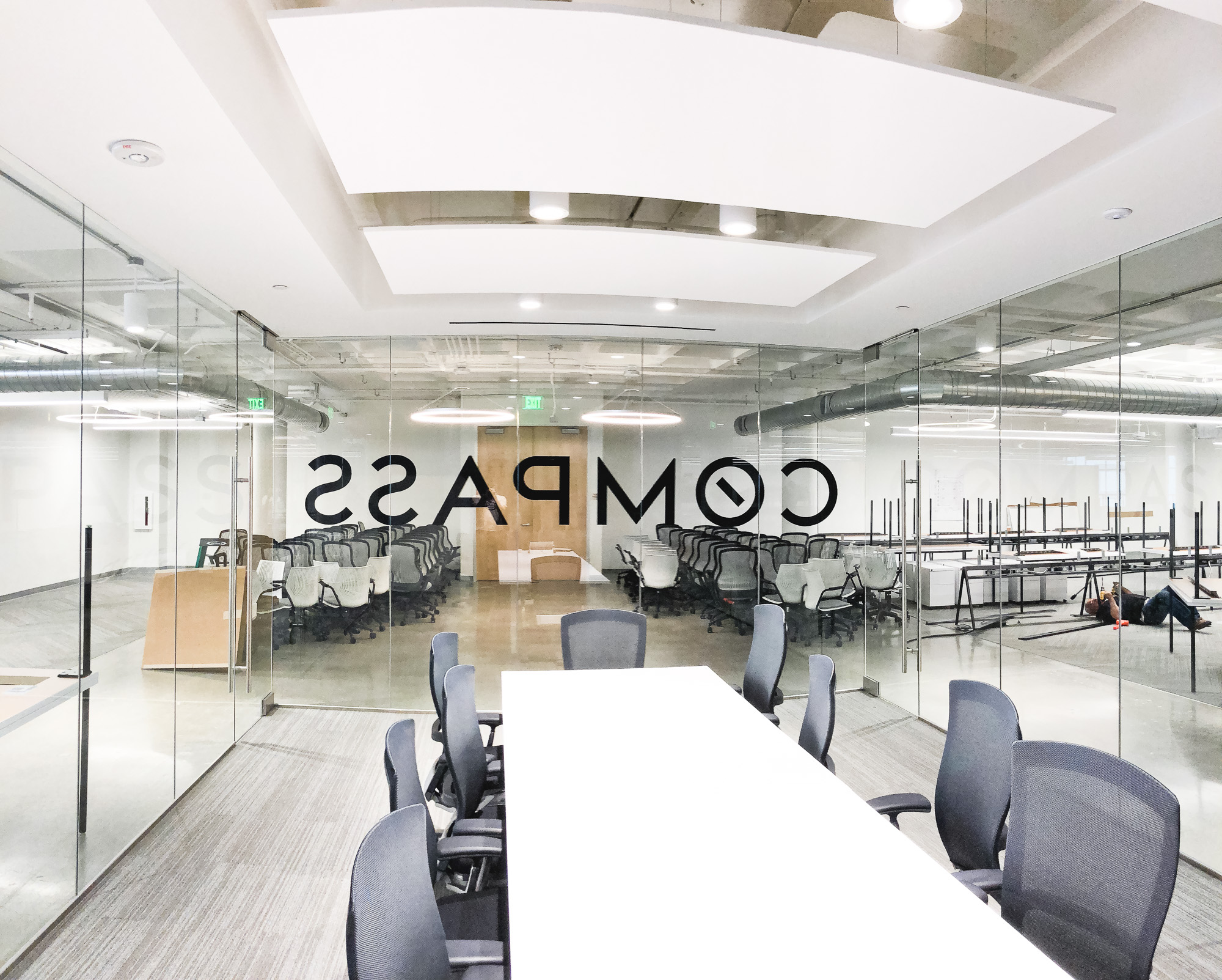 Glass vinyl sign / privacy screen at the San Francisco office of Compass, a modern real estate platform.