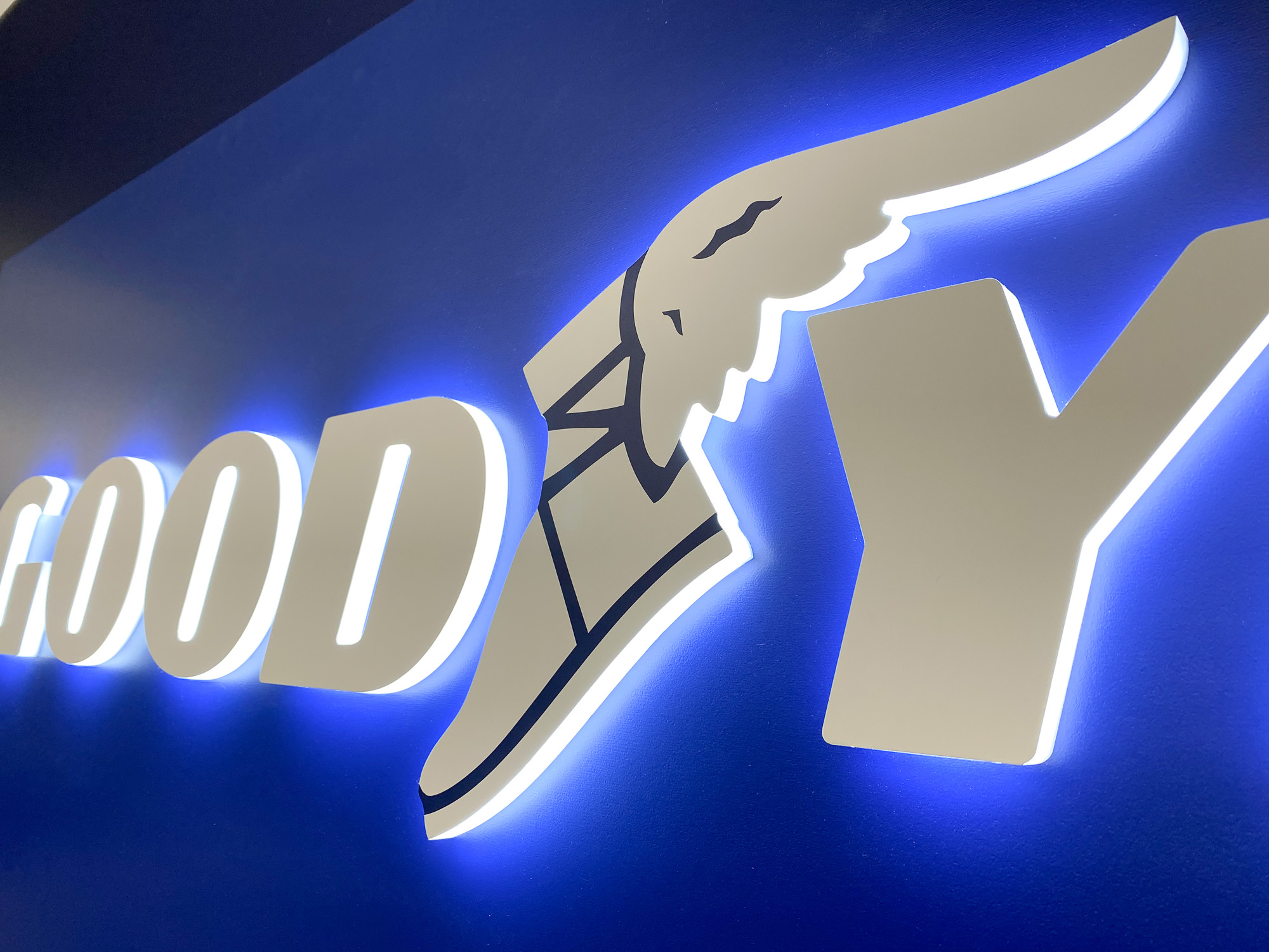 Illuminated, blue, edge-lit lobby sign behind reception desk for the San Francisco office of Goodyear, a tire manufacturer.