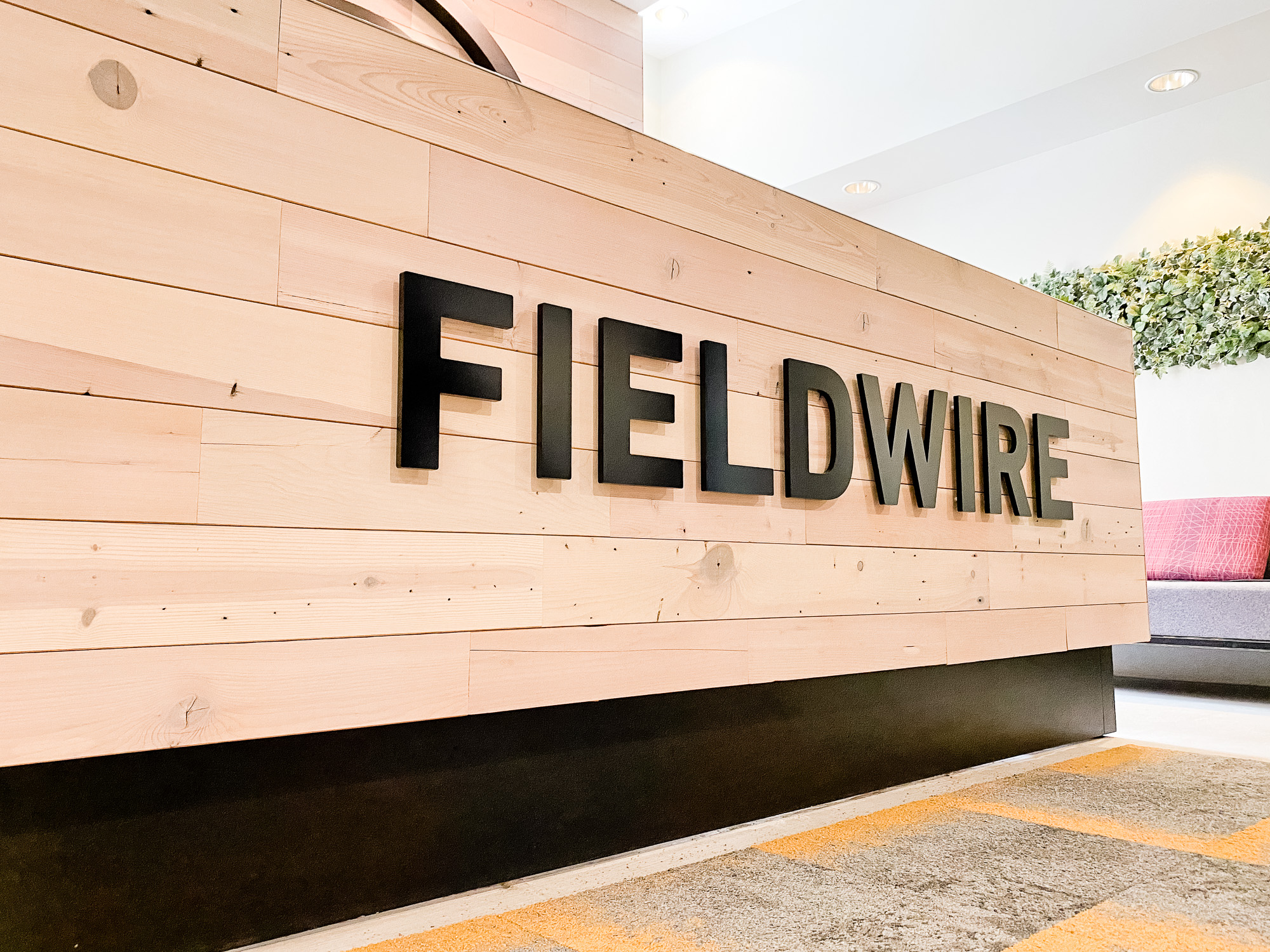 Dimensional black reception wall and desk sign for the San Francisco lobby of Fieldwire, a company creating a construction field management platform designed for the jobsite.