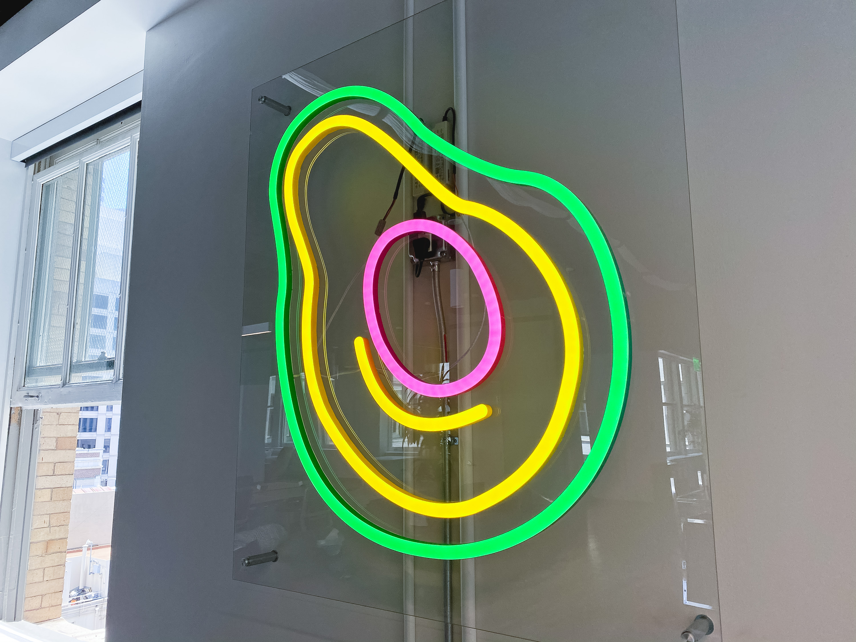 Neon avocado sign with clear acrylic backer on white wall for the San Francisco office of Meltwater, a software as a service company that develops and markets media monitoring and business intelligence software.