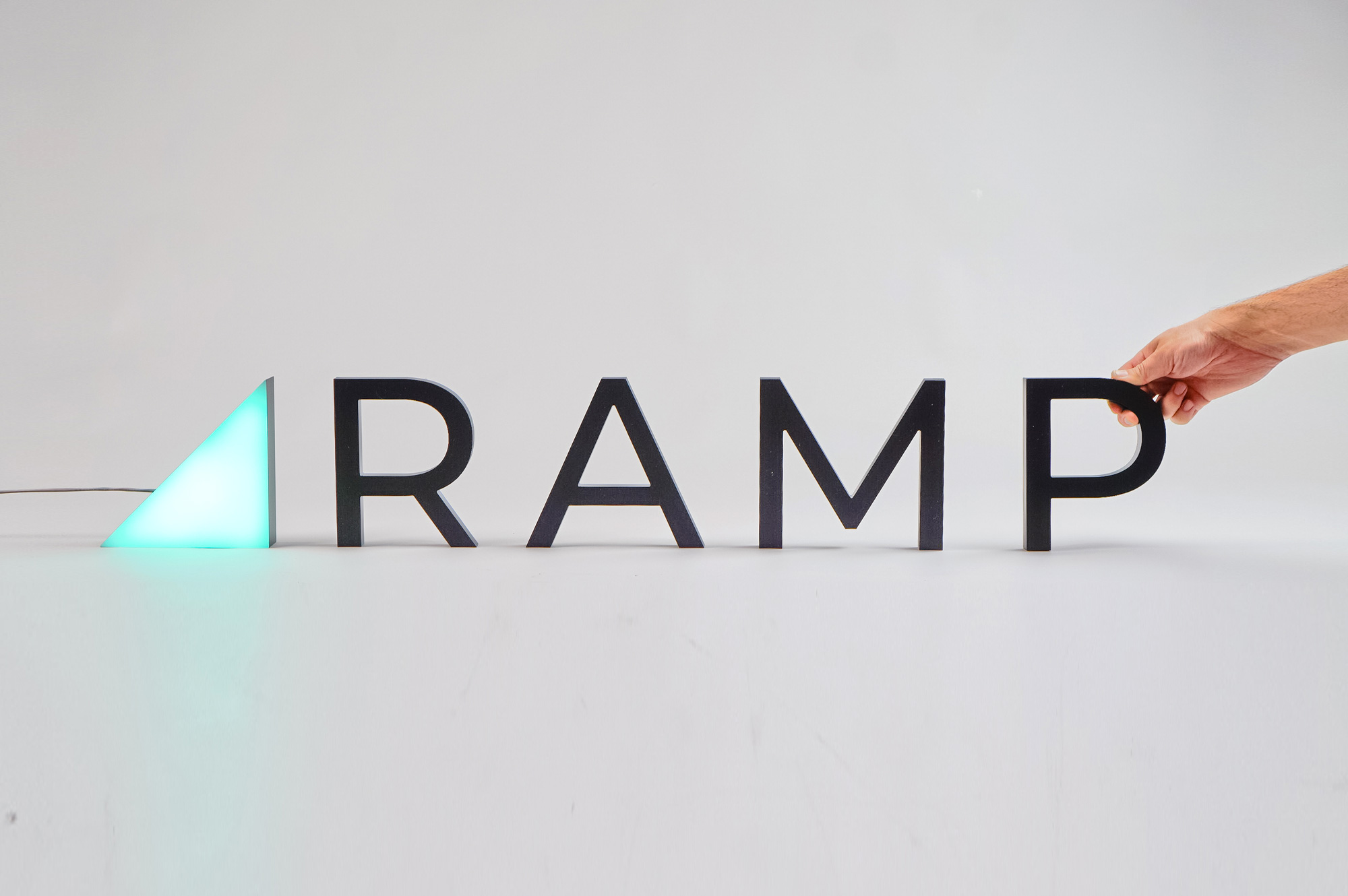 Illuminated, freestanding green triangle and black letters for Ramp, a technology company building the next generation corporate card to save businesses money.