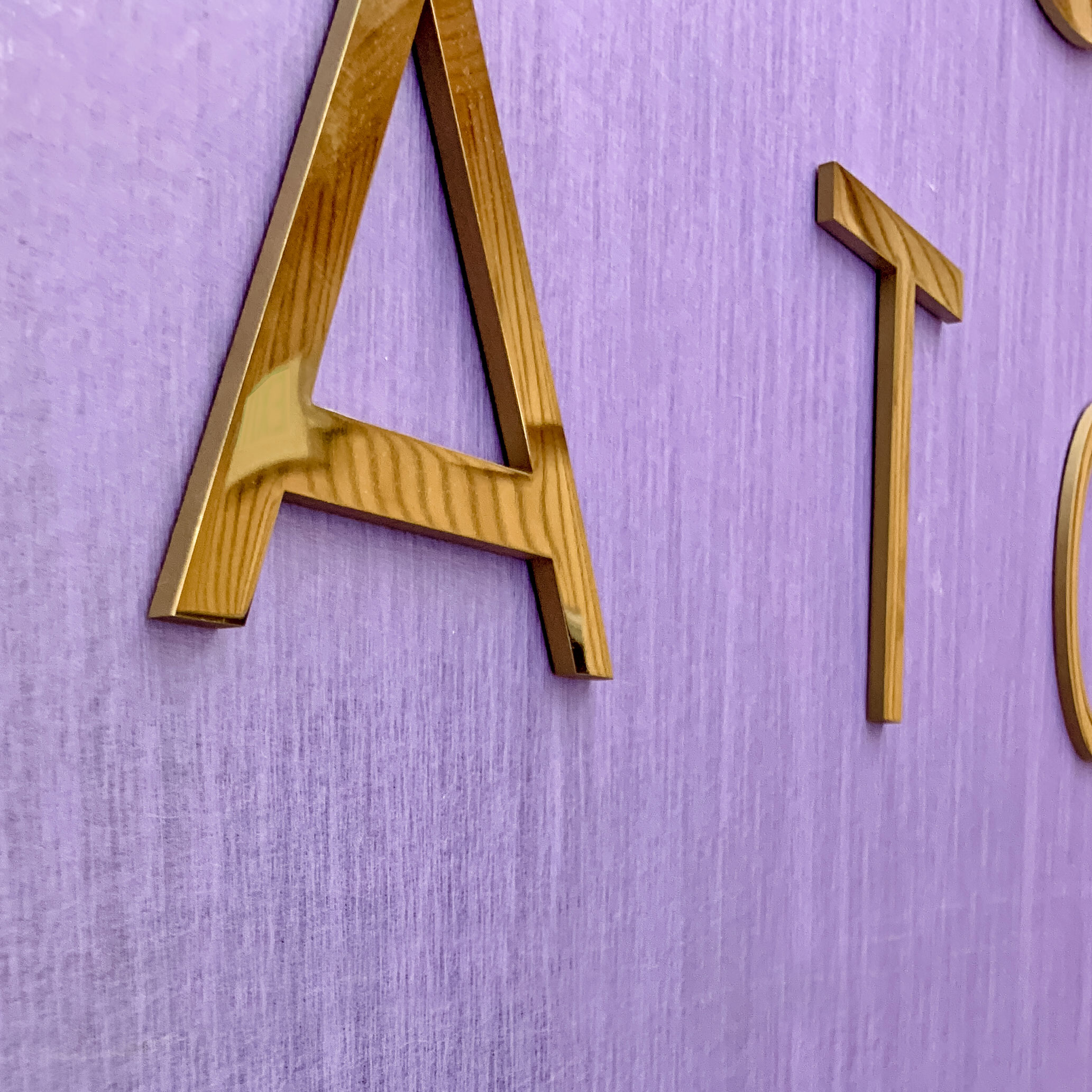 Solid polished brass sign on purple silk wall for the lobby at Tatcha, a company that creates luxury Japanese beauty products.