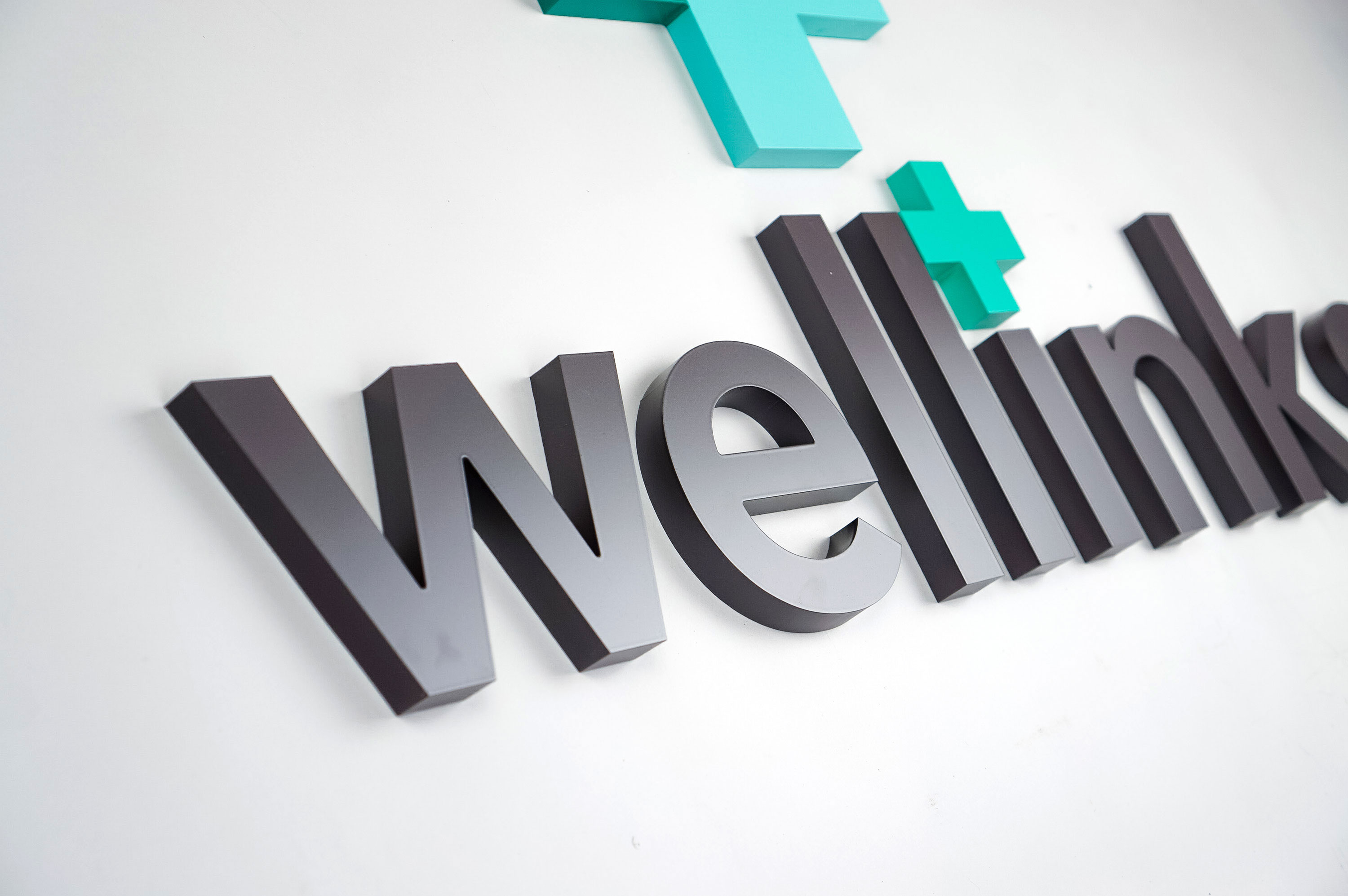 Green and grey lobby/reception logo sign for Wellinks, a wearable health technology company based in New Haven, Connecticut.