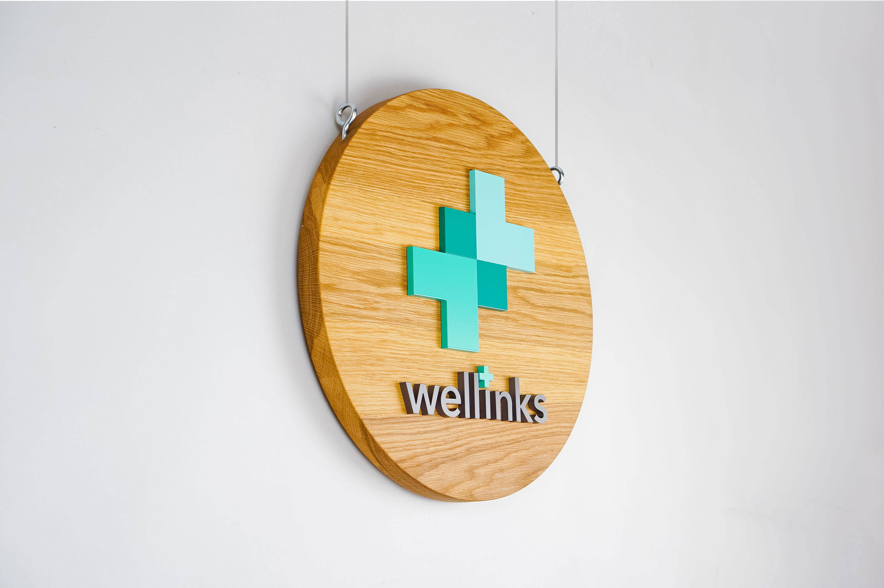 Wood hanging blade sign with green and grey logo for Wellinks, a wearable health technology company.