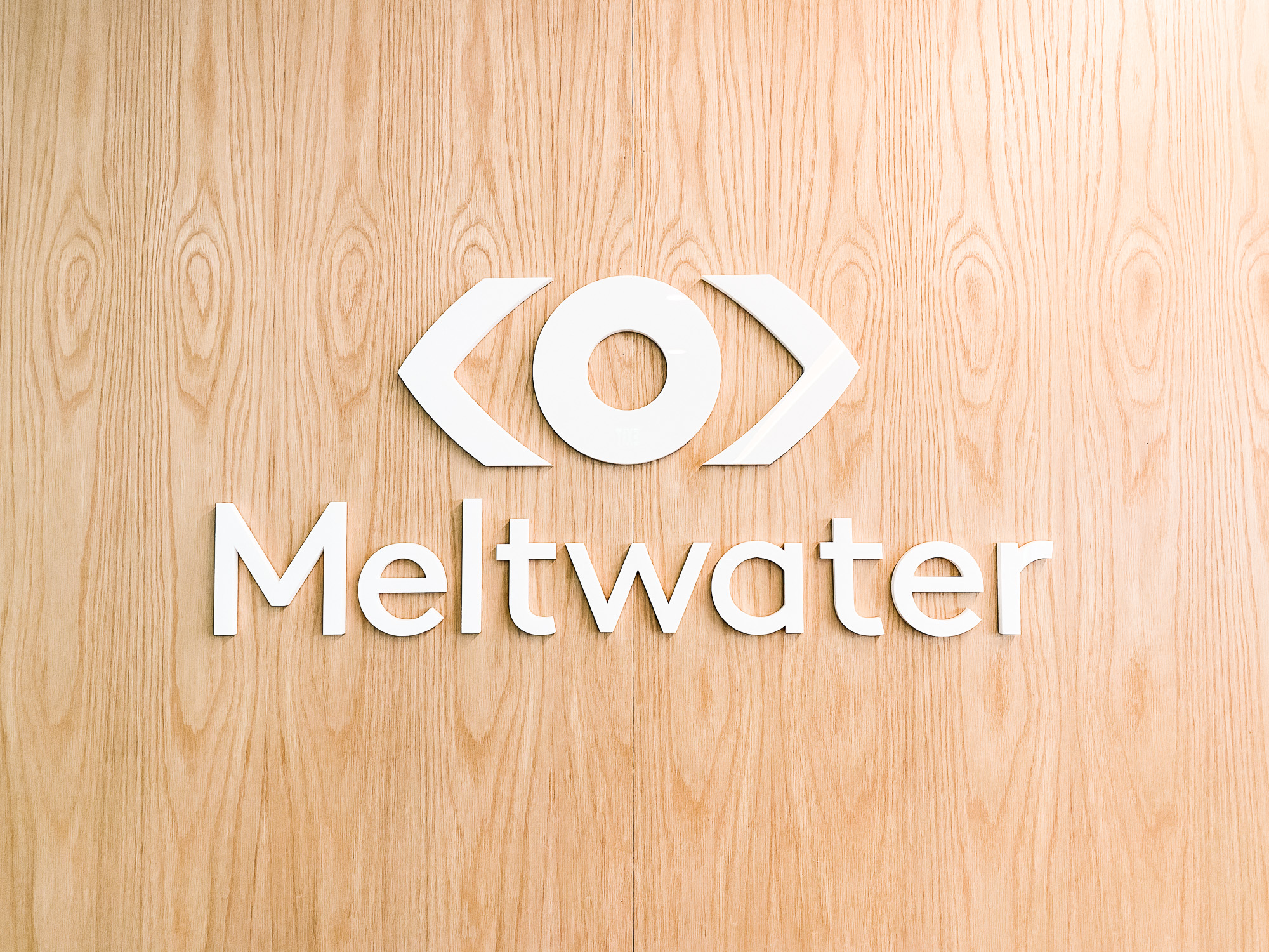 White logo on light wood add-on divider wall for the San Francisco office of Meltwater, a software as a service company that develops and markets media monitoring and business intelligence software.