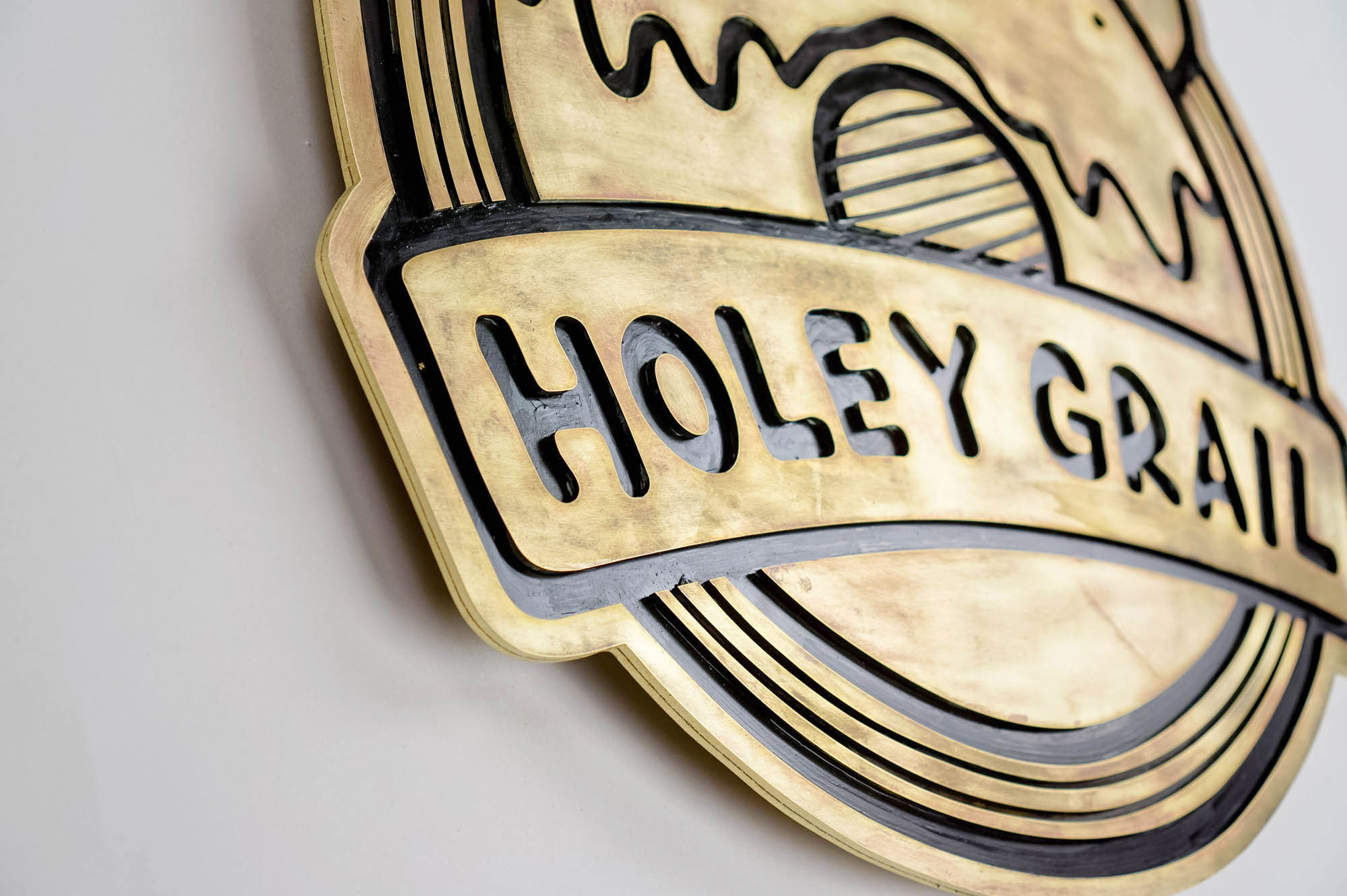 Patinated, retro brass sign for Holey Grail, a donut shop based in Hawaii.