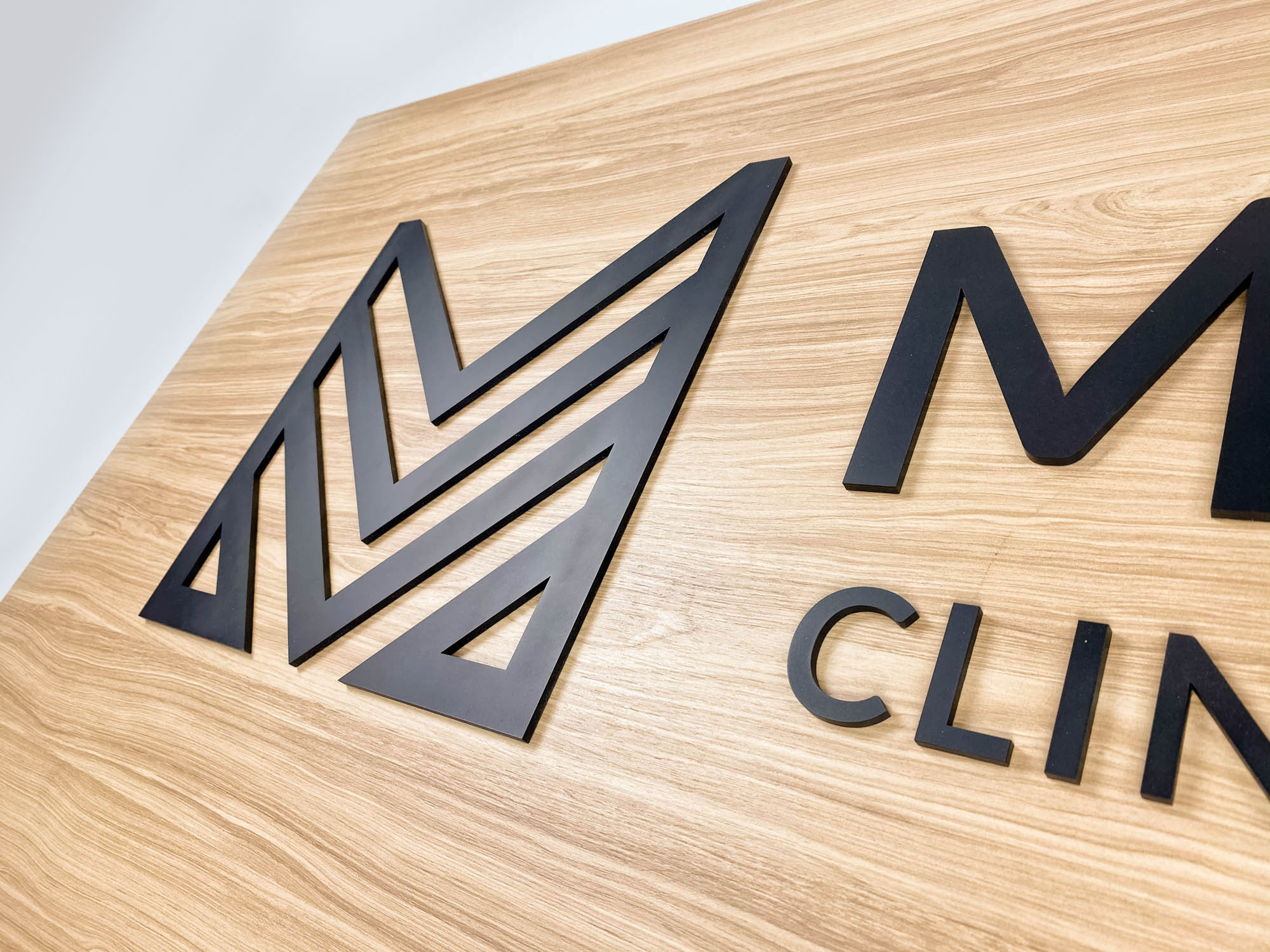 Black logo on light wood laminate panel for the Midtown Clinic of Chiropractic, a full-service chiropractic treatment center serving the Lake Worth, FL area.