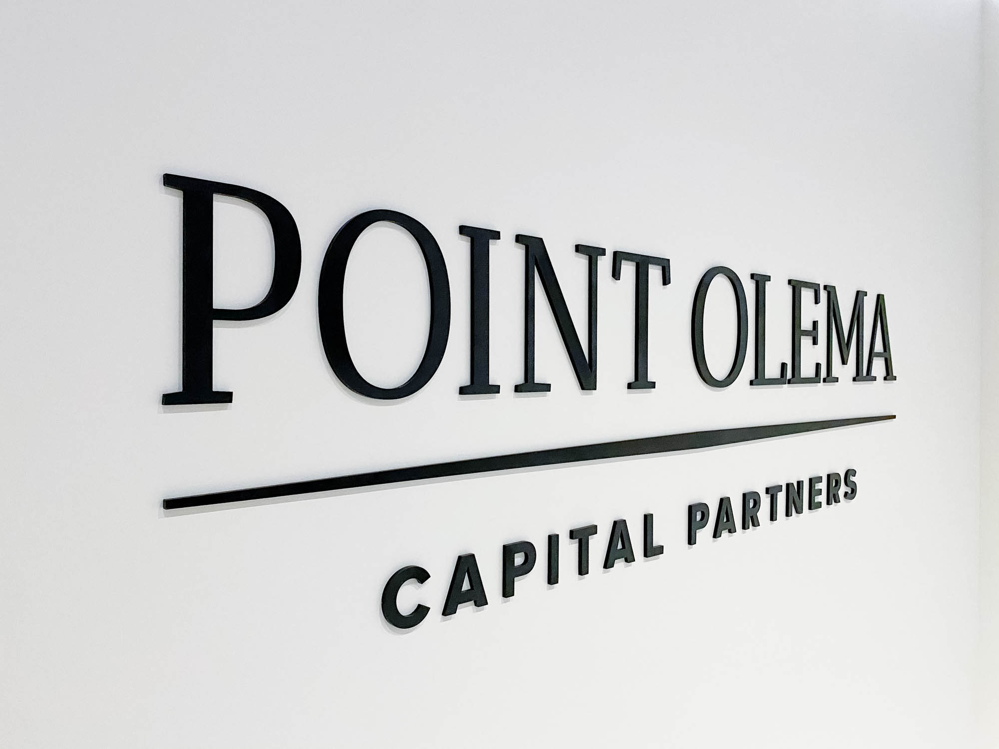 Simple black lobby sign on painted wall with uplights for the San Francisco office of Point Olema Capital Partners.