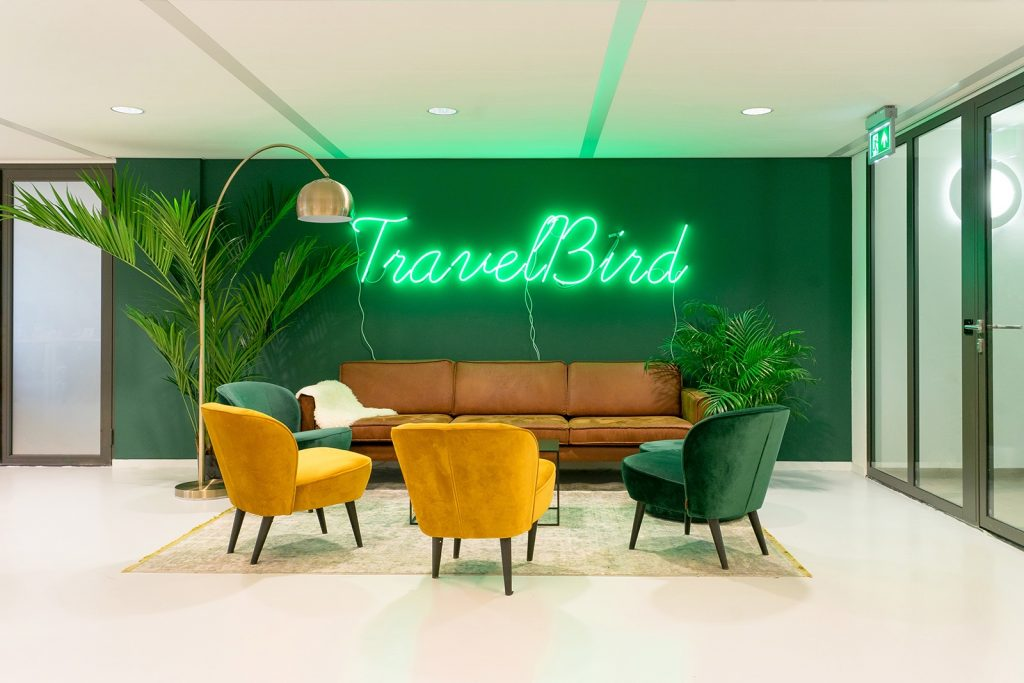 Green neon sign on green painted wall for the lobby of Travelbird, in Amsterdam, Netherlands. (Photo: June Studio Amsterdam)