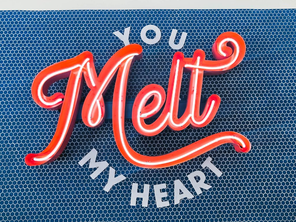 Retro, red neon sign in red channel letters on blue tile wall for The Melt, a restaurant in San Francisco, CA.