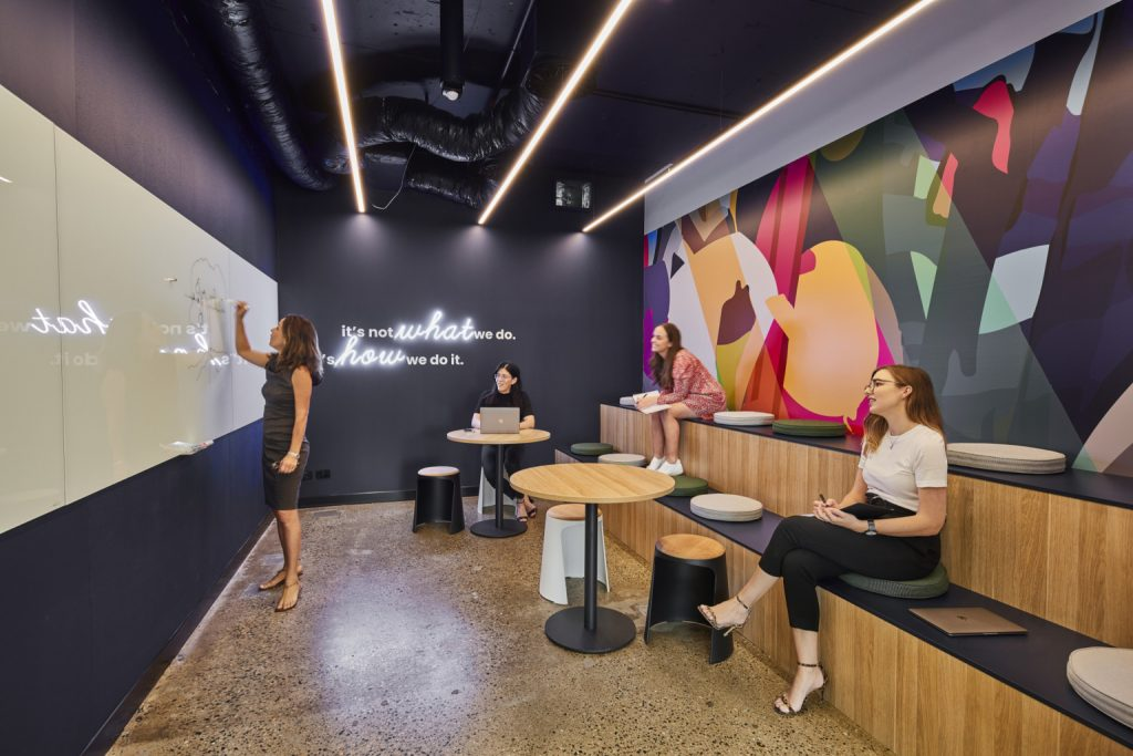 Neon motto on black wall in tiered seating office room at Over the Wire in Brisbane, Australia. (Photo: Cieran Murphy Photography)