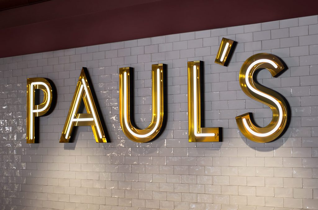 Neon sign in gold open face channel letters on white tile wall for Paul, a restaurant in Stockholm, Sweden. (Photo: 25AH)