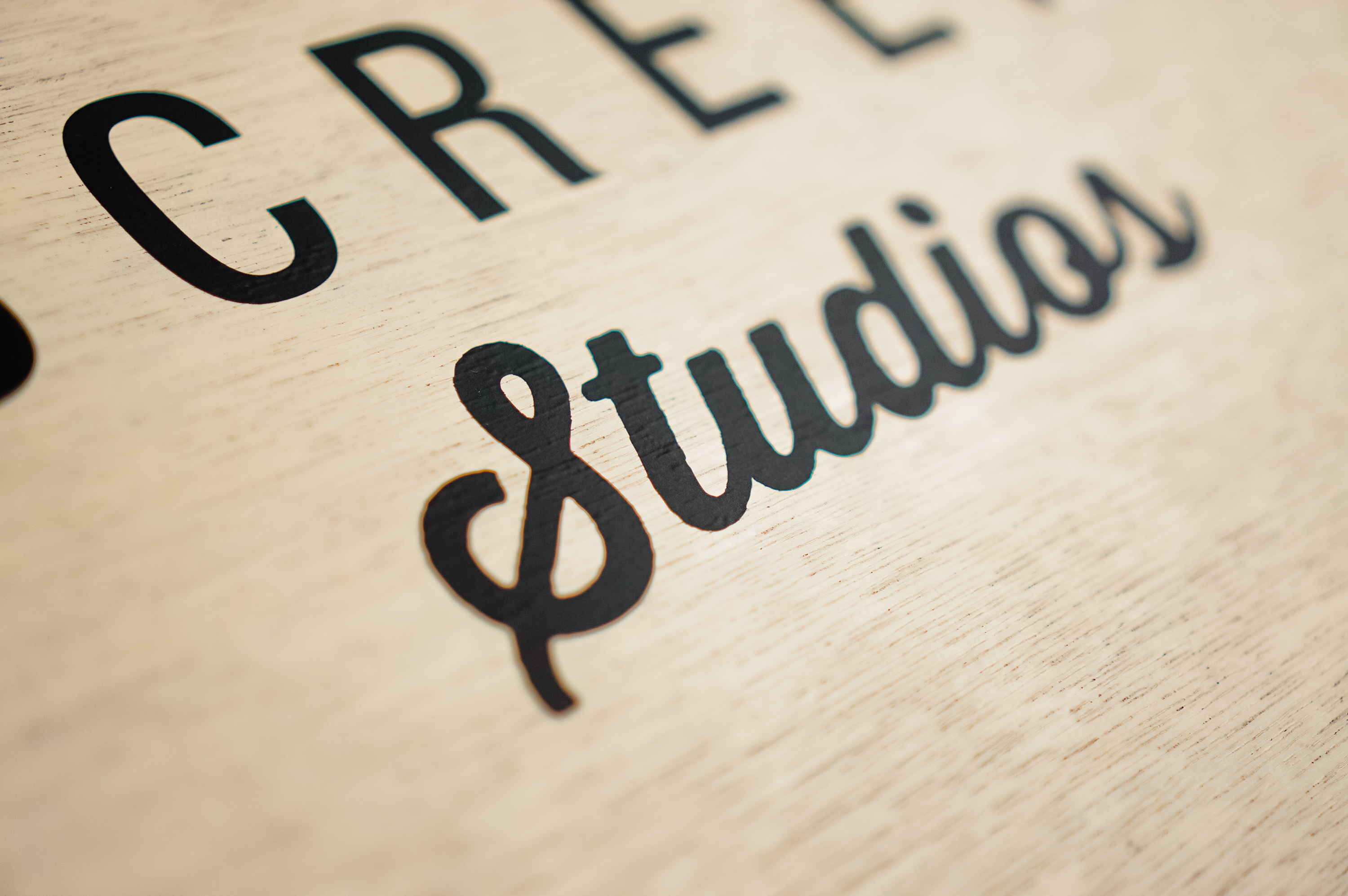 Wood hanging blade sign with black artwork for the storefront of Small Screen Studios, a shop in Cleveland, OH.