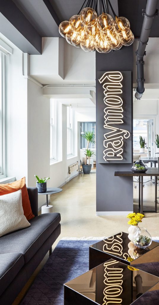 White neon sign with clear backer on grey painted wall for the office of Raymond in New York. (Photo: Seth Caplan)