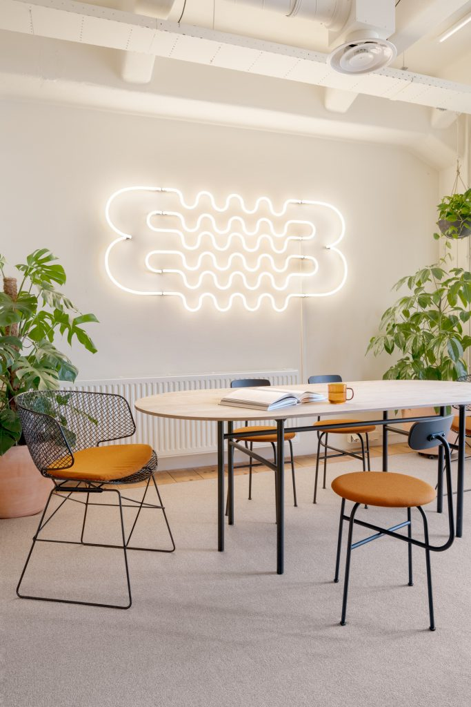 White neon squiggle in modern office conference room.