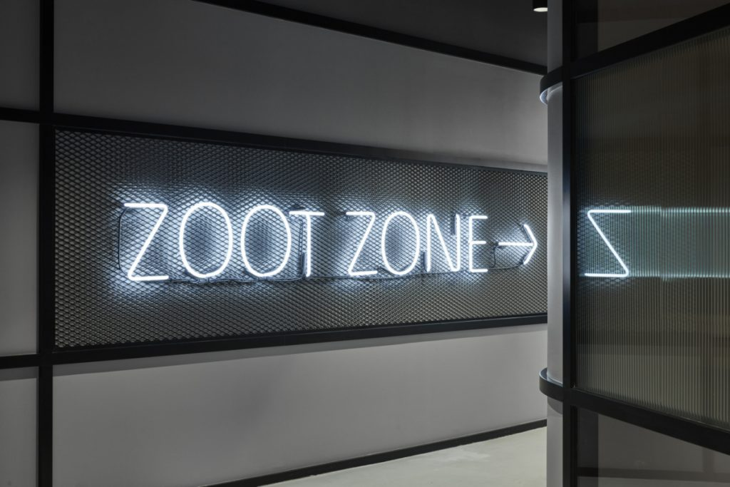 White neon Zoot Zone sign on metal cage/grid for the office of Deswik in Fortitude Valley, Australia. (Photo: Cieran Murphy)