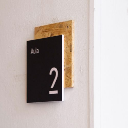 Black room sign with cork backer and white text for ISIA in Firenze, Italy.