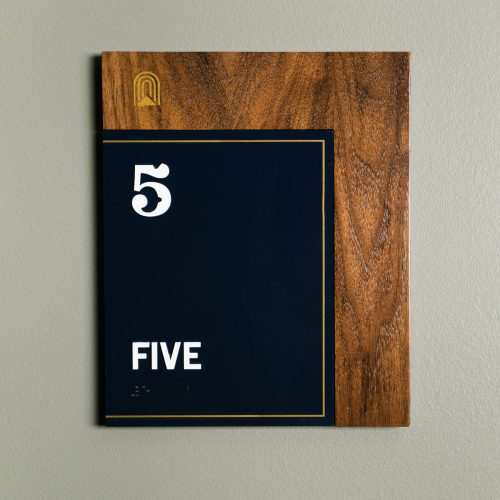 Retro style black and walnut room sign with white and brass details, designed by Studio Mast for The Ramble Hotel, a French Salon inspired hotel in Denver's fastest growing neighborhood.