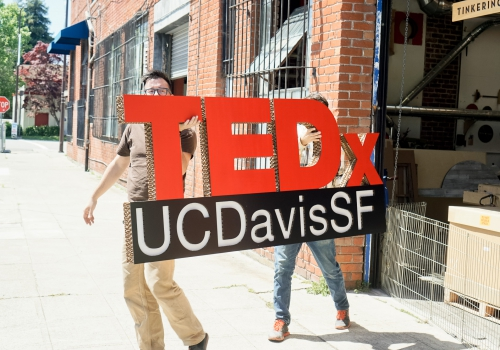 carrying large TEDx stage sign