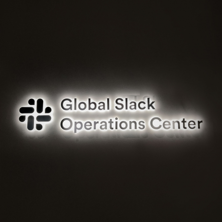 Brushed metal sign with edge lit lighting for the operations center of Slack, an American cloud-based set of team collaboration tools and services.
