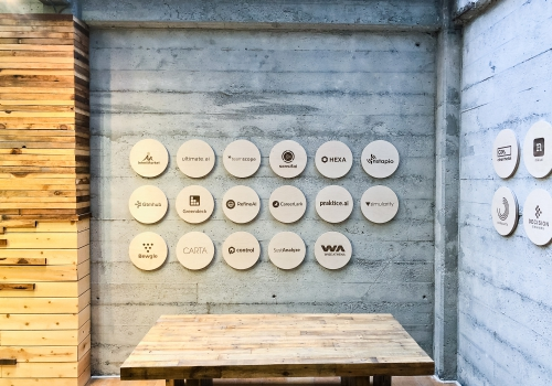 Wall of etched wood plaques with logos for SAP.io in San Francisco