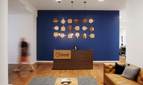 Modern, light wood engraved panel sign for the front lobby desk at Bread, a company that creates point-of-sale financing technologies.