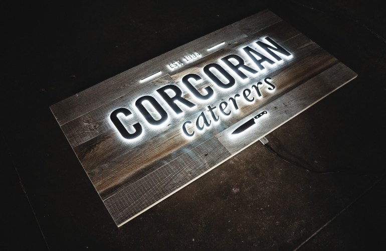 Reclaimed barnwood sign with push-through illuminated lettering for Corcoran Caterers, an event catering company serving the Washington DC area.
