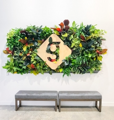 Light wood sign with colored edges on living wall for the lobby of Getaround, an online car sharing or peer-to-peer carsharing service.
