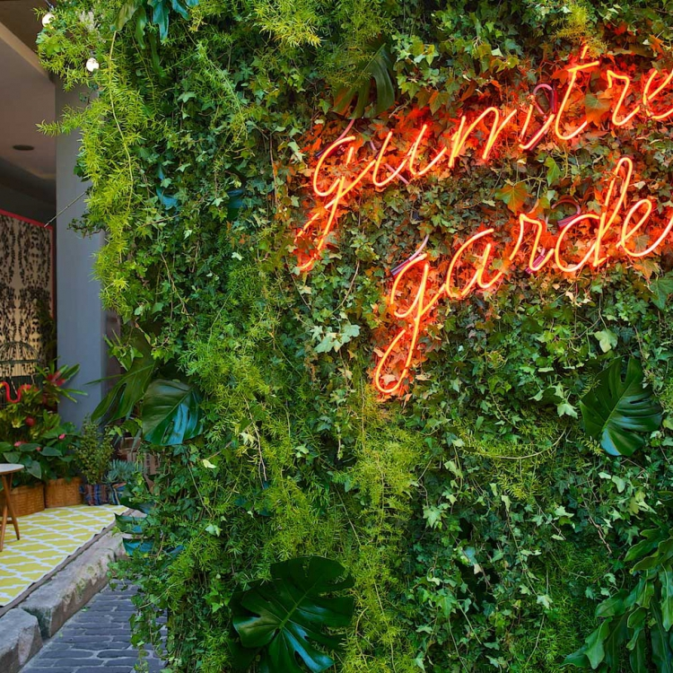 Red neon sign on living wall at Gumtree Garden event