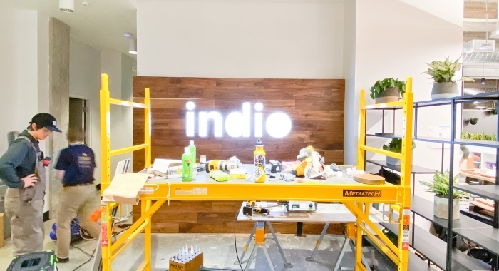 Full wall installation with dark wood and an illuminated, built-in logo for the San Francisco lobby of Indio, a company that simplifies the insurance application process for brokers and their clients.
