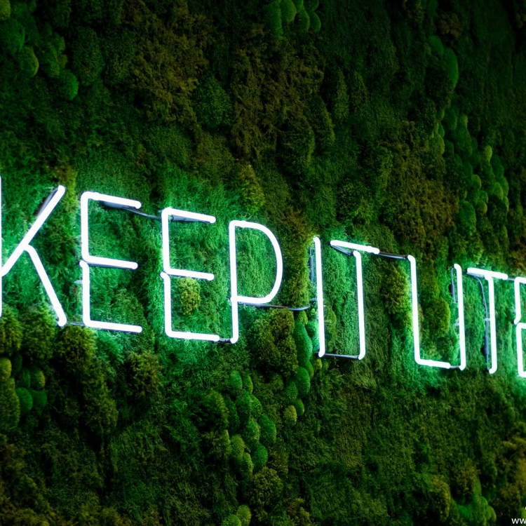 Neon sign on moss wall saying
