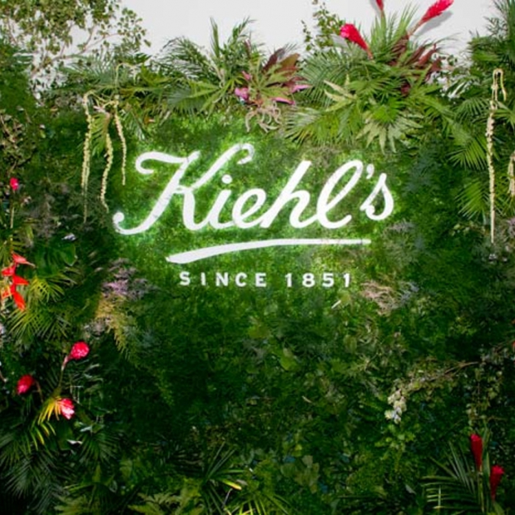 Illuminated sign on living wall at Kiehl's event
