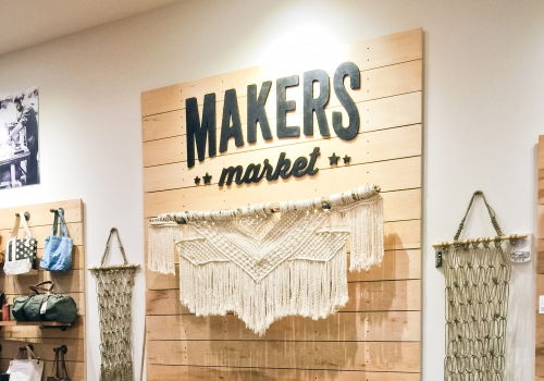 Black and wood interior sign behind cash register for Maker's Market