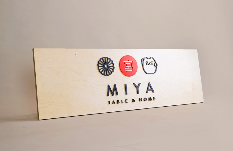 Raised black, red, and light wood sign with icons for Miya Table & Home, a third-generation family owned business, importing Japanese tableware and gifts since 1947.