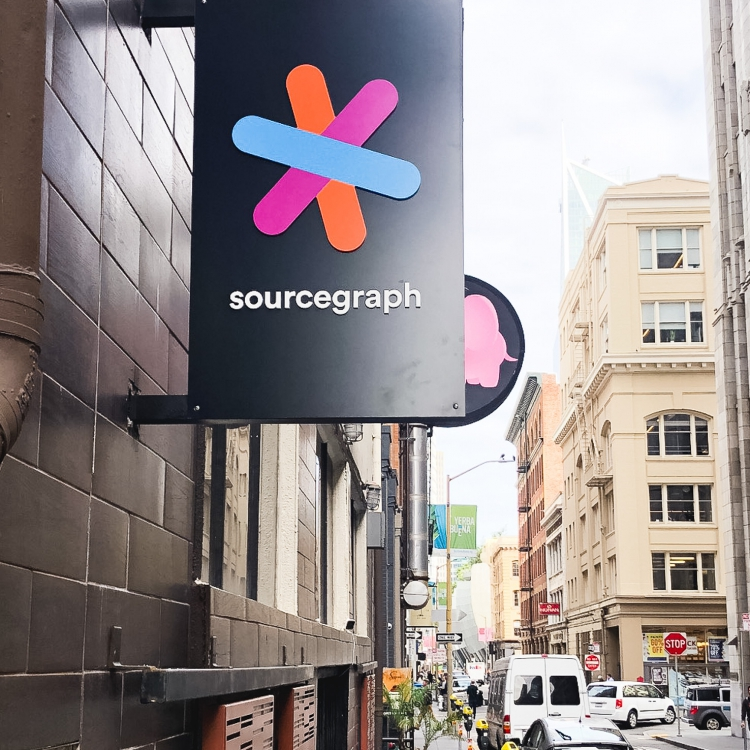 Simple black blade sign with colored logo for Sourcegraph, a San Francisco-based company that adds code intelligence to GitHub and other code hosts.