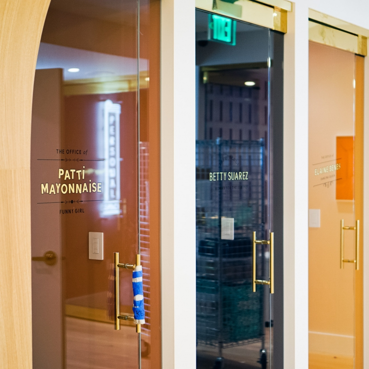 23k gold leaf signage honoring the names of iconic women, on glass doors at The Wing San Francisco, a co-working space for women.